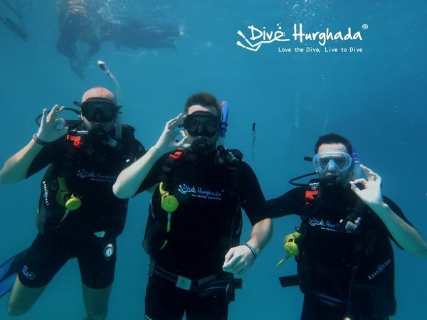 Happy divers underwater scuba diving with Dive Hurghada team